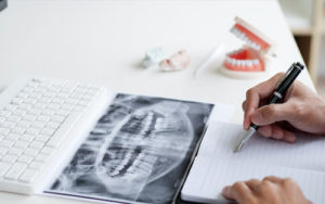 dentist looking at xrays for dental crowns and bridges